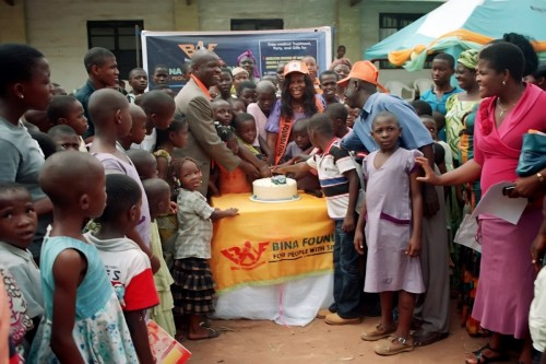 Childrens cutting of cake with The President of Bina Foundation