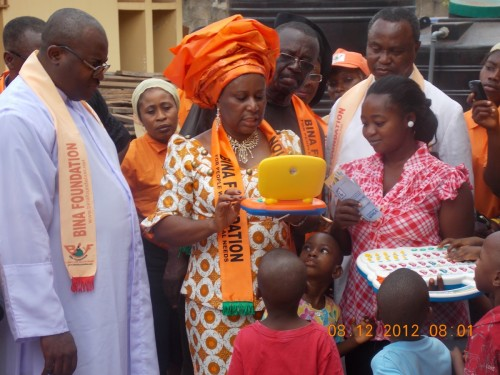 The president of bina foundation presenting gifts to the motherless babies